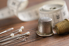 Sewing Items - Thimbles, Including Pins, Measuring Tape On Background.