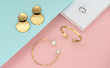 Top View Of Golden Women Accessories On Pastel Colors Background