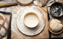Kneaded Dough Of White Wheat Flour Lies On A Round Wooden Board, A Metal Bucket And A Wooden Rolling Pin