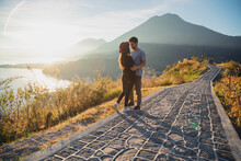 Young Couple Seeing Each Other Face To Face Overlooking Lake Atitlan At Sunrise - Traveling Couple In Love At The Lake Viewpoint In Guatemala