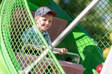 Smiling Cute Boy Sitting At Amusement Park Ride