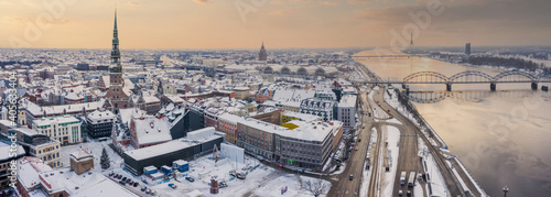 Aerial view photo from flying drone panoramic to St. Peter's Church and the Old Riga Town in the background of the Daugava River and downtown on a beautiful early winter morning. © ingusk