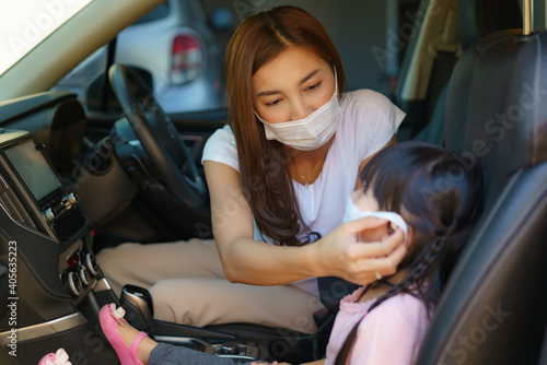 Asian mother help her daughter wearing protection mask to protect the coronavirus Covid-19 outbreak situation before in car go to school. Get ready to school concept..