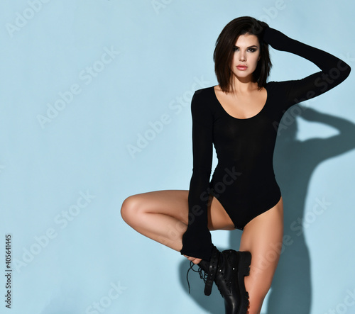 Young beautiful sexy brunette woman in black sport jumpsuit and massive boots standing with leh on knee touching hair over blue background, copy space. Beauty of woman body and perfect shape concept