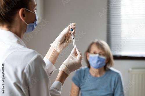 Obraz elderly woman getting coronavirus vaccine - fototapety do salonu