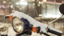 The Steering Wheel And Headlight Of A Moped Covered With Snow During A Cyclone On A City Street In The Evening. Close-up. Urban Winter Landscape