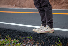 Low Section Of Man Standing On Roadside