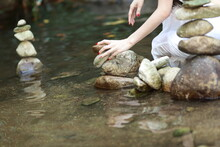 Midsection Of Woman Stacking Stones At River
