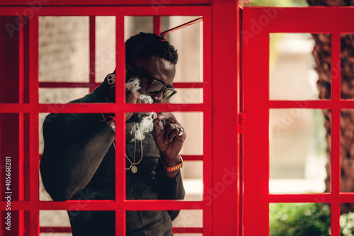 portrait of african model using smartphone while smoking cigar in telephone booth