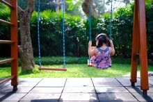The Back View Of A Lonely Young Asian Girl Playing On A Swing By Herself In An Empty Playground On A Sunny Day.