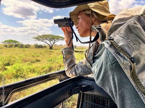 Woman Looking Through Binoculars In Vehicle At Serengeti National Park - fototapety na wymiar