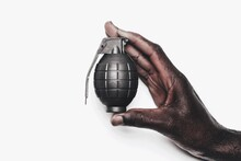 Close-up Of Hand Holding Grenade On White Background