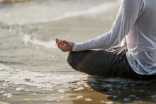 Midsection Of Man Meditating At Beach During Sunset