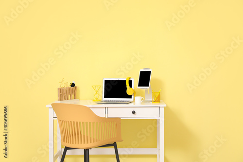 Obraz Stylish workplace with modern gadgets against color wall in room - fototapety do salonu