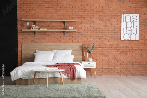Interior of bedroom with brick wall