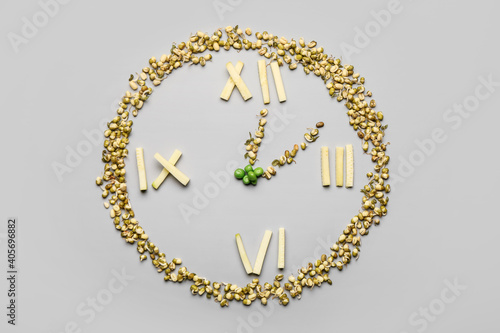 Obraz na plátně Clock made of food on grey background