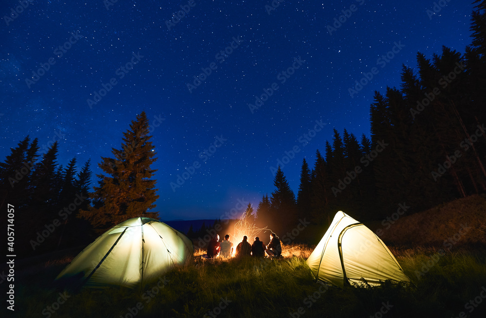 Fototapeta Rear view, tourists are sitting by brightly blazing bonfire between the tents against the backdrop of mountain valley and pine forest under blue night sky with bright stars. Outdoor activity concept - obraz na płótnie