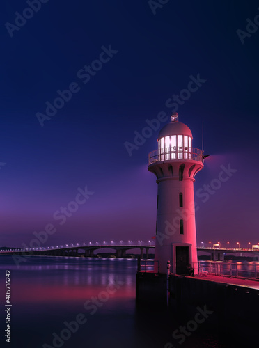 Illuminated Lighthouse By Sea Against Sky At Night