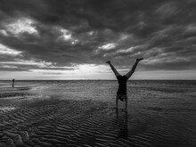 Child With Handstand On Beach Against Sky During Sunset