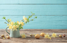 Golden Easter Eggs And Yellow Flowers On Wooden Background