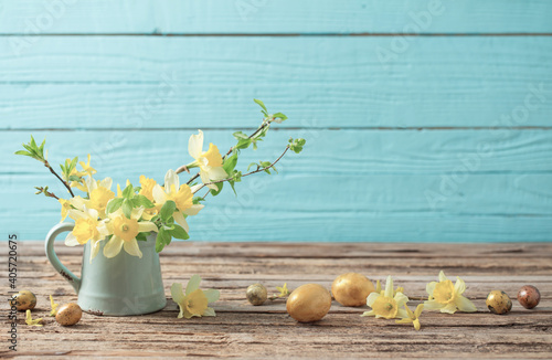 Obraz Golden Easter eggs and yellow flowers on wooden background - fototapety do salonu