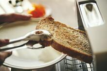 食パンをトースターから取り出す