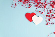 Valentine's Day Background. Two Hearts With Red Confetti, Beads With Hearts On Pastel Blue Colors. Valentine's Day Concept. Flat Lay. Top View.