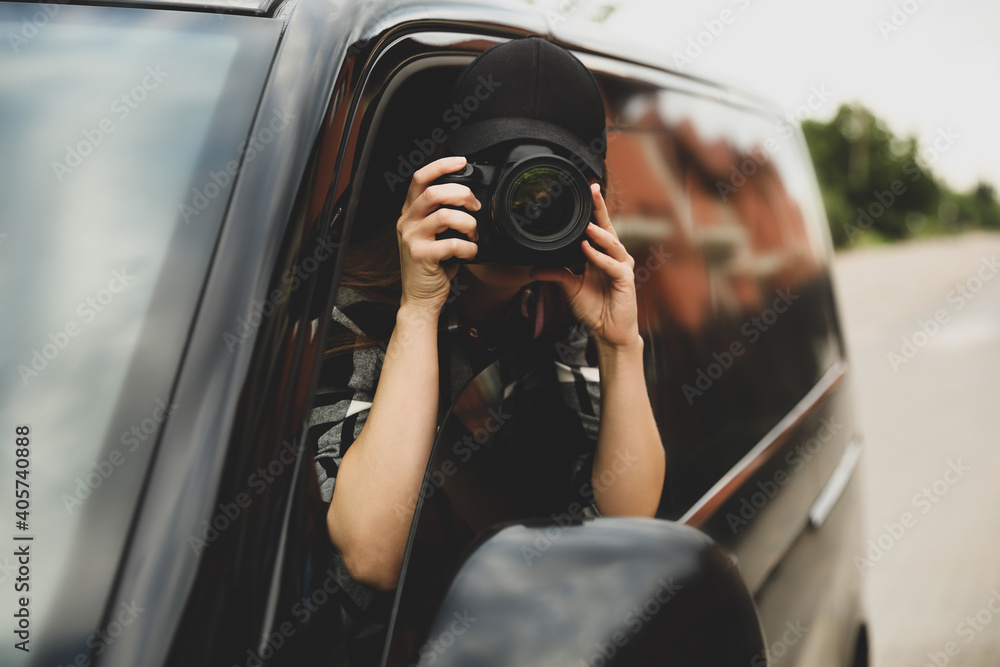 Fototapeta Private detective with camera spying from car