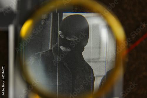 Looking at detective board through magnifying glass, closeup
