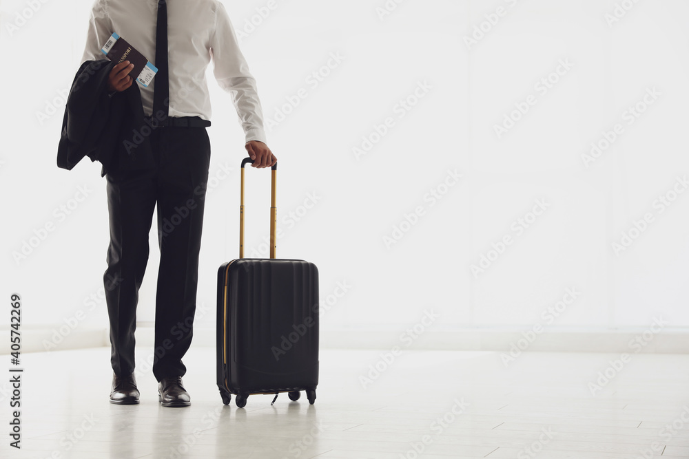 Fototapeta Businessman with black travel suitcase in airport. Space for text