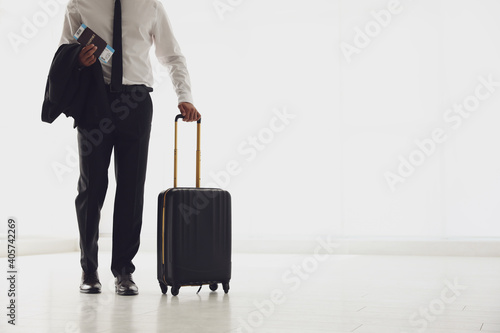 Fotografie, Obraz Businessman with black travel suitcase in airport. Space for text