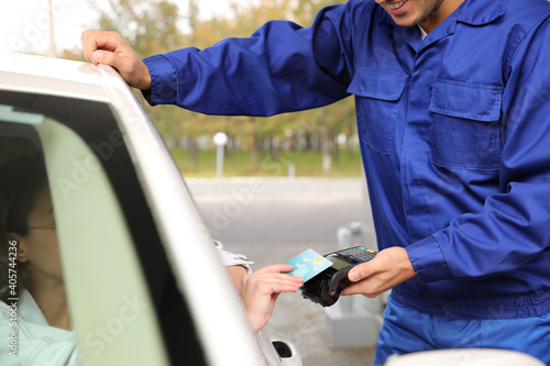 Woman sitting in car and paying with credit card at gas station, closeup