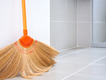 Straw Broom Leaning Against White Door On Brown Tile Floor Backdrop With Copy Space, Equipment For Housework, Home Cleaning.