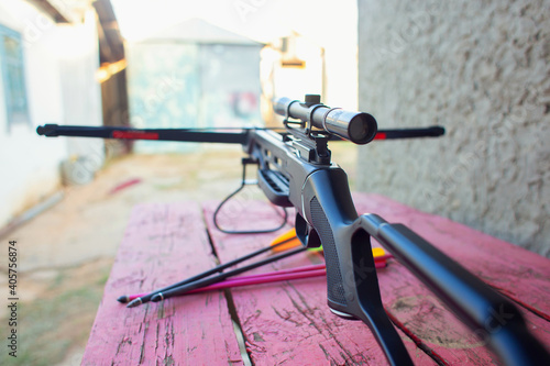 A modern crossbow with arrows and a telescopic sight lies on a wooden table in the street Fotobehang