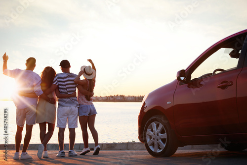 Group of friends near car outdoors at sunset, back view. Summer trip
