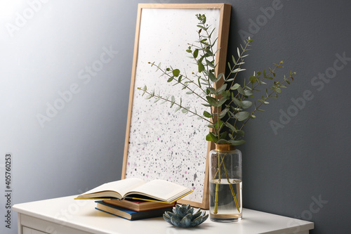 Obraz Beautiful eucalyptus branches on white table near black wall in modern room. Interior design - fototapety do salonu