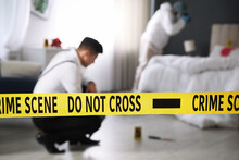 Investigators Working At Crime Scene In Messy Room, Focus On Yellow Tape