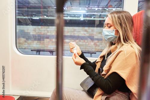 Pendlerin mit Maske in der Bahn beim Hände desinfizieren