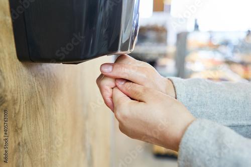 Obraz Kundin am Desinfektionsspender am Supermarkt Eingang - fototapety do salonu