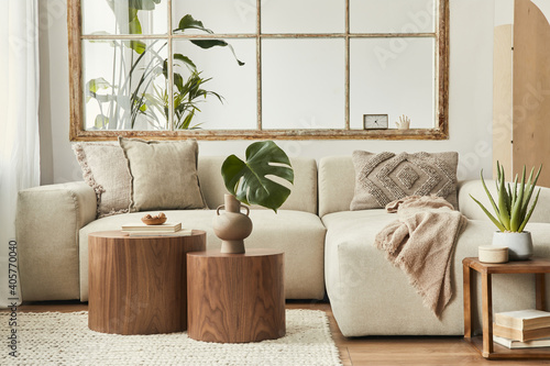 Fotografía Interior design of living room with stylish modular beige sofa, wooden coffee tables, plants, pillows, plaid, neutral room divider, decoration and elegant accessories