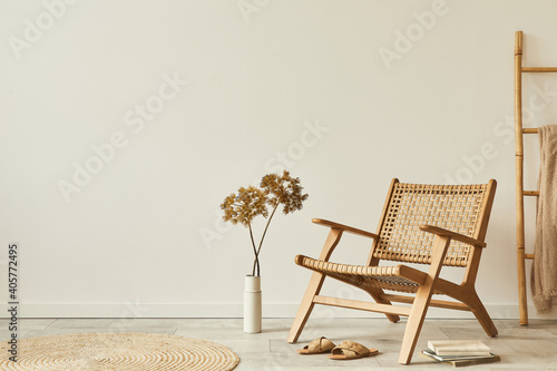 Neutral concept of living room interior with design wooden armchair, round carpet, dried flowers in vase, slippers, decoration and elegant personal accessories. Template. Copy space.