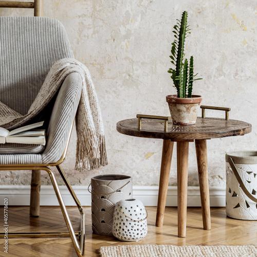 Obraz Stylish oriental living room with design armchair, beautiful macrame, carpet, decorations and elegant personal accessories in wabi sabi concept. - fototapety do salonu
