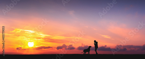 Obraz The girl is walking, enjoying a beautiful and rich sunset with her beloved pet - fototapety do salonu