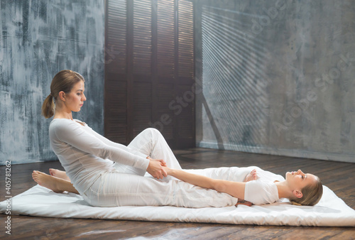Obraz Young woman is getting Thai massage treatment by therapist. Traditional Asian stretching therapy. - fototapety do salonu