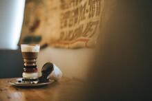 Café Preparado. Bebida De Café Asiático Sobre Mesa De Cafetería. Capas De Café, Leche Condensada, Licor Y Crema De Diferentes Colores. Vaso De Cristal Con Café.