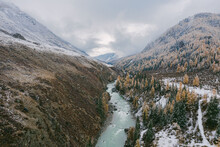 The Blue River Flows Among The Mountains In Autumn In Altai