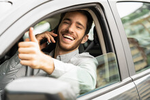 Young Man Showing Thumbs Up Sign In Car