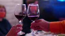 Close Up And Soft Focused View Of Twa Wine Glasses Half Filled With Wine In Hands Of Man And Woman. Defocused View Of Background.