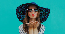 Portrait Close Up Of Beautiful Young Woman Blowing Her Red Lips Sending Sweet Air Kiss Wearing A Summer Straw Hat On A Blue Background