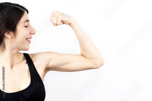 Valokuvatapetti Young woman biceps in fitness wear isolated on white background.